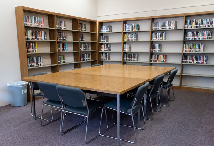 library room with shelves of books and big table in middle with chairs