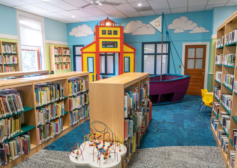 childrens room in library with bright carpet and wall and toy boat