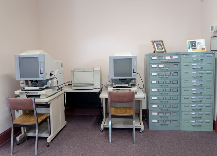 desk with old computers next to old filing cabinet