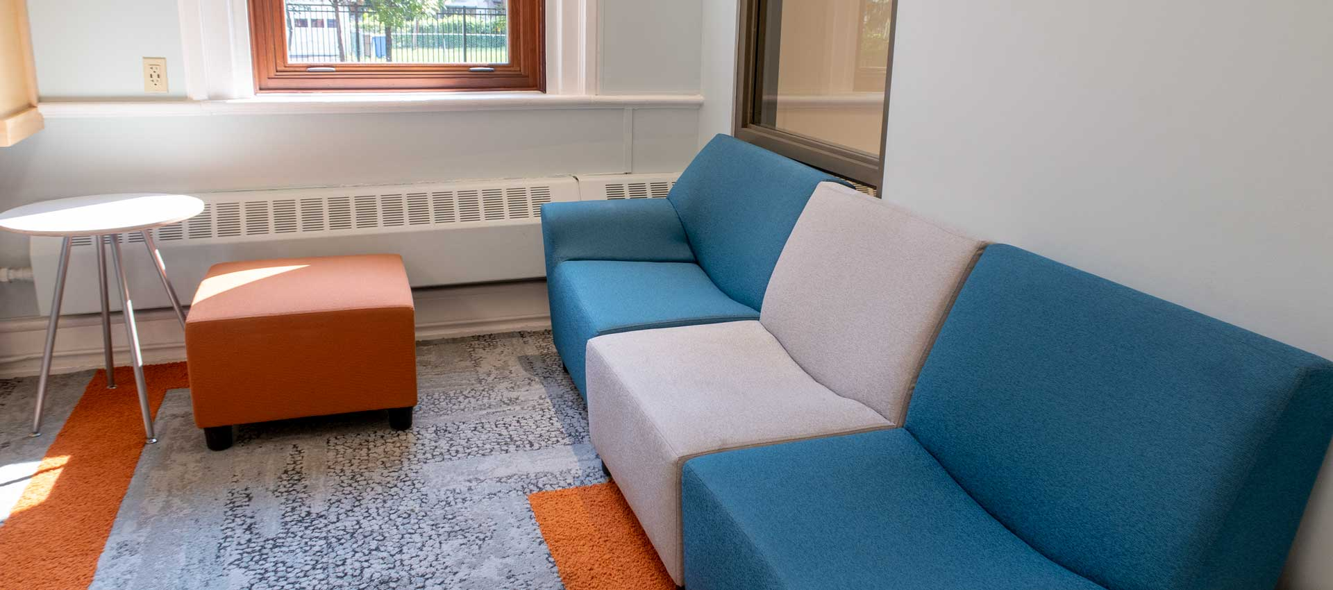 couch and ottoman with side table in library teen room