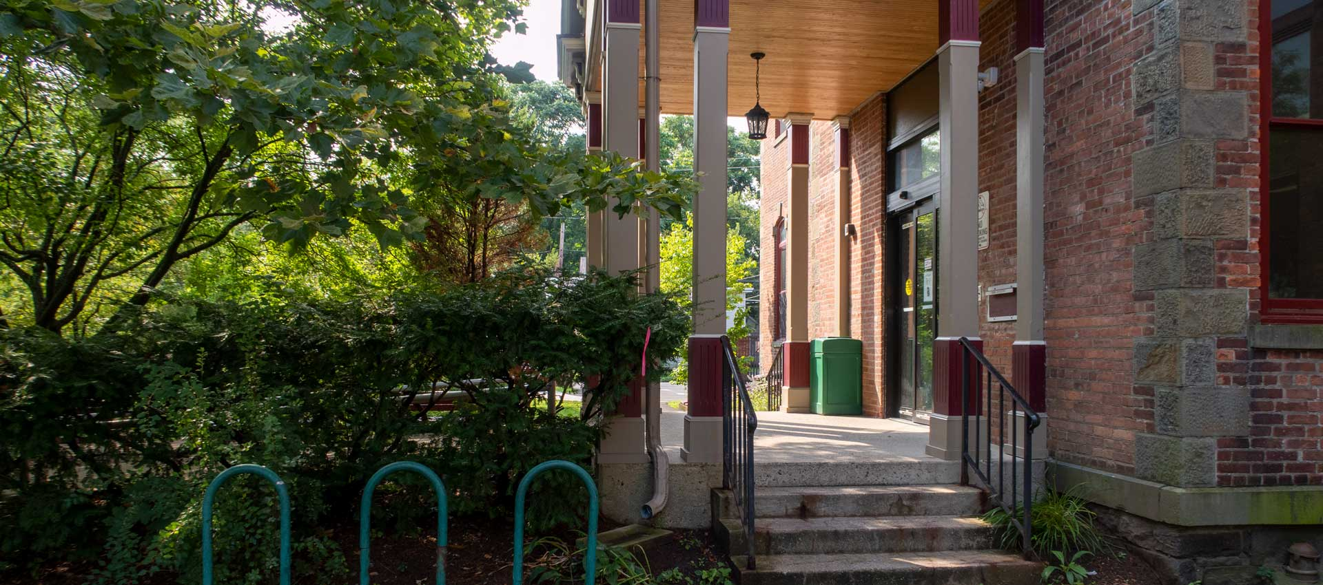 side entrance to library with stairs and greenery